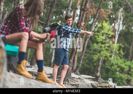 young couple with backpacks on hiking trip in forest - Stock Photo