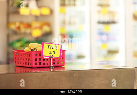 school canteen tuck shop cafeteria selling healthy fruit food options for students. bananas in a red tray on stainless steel bench in foreground - Stock Photo