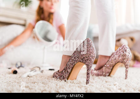 partial view of little girl wearing mothers high heels at home - Stock Photo