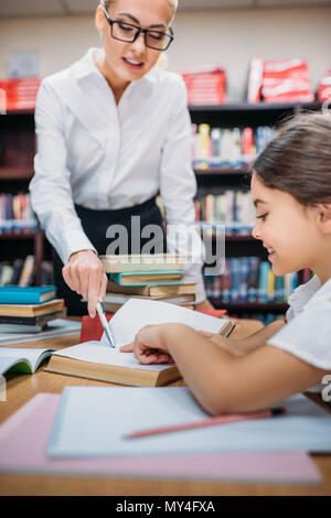 close-up view of young teacher helping adorable schoolgirl with homework in library - Stock Photo