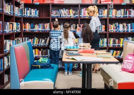 young teacher with kids learning in library - Stock Photo