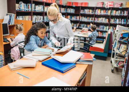 young teacher helping schoolgirl with homework in library
