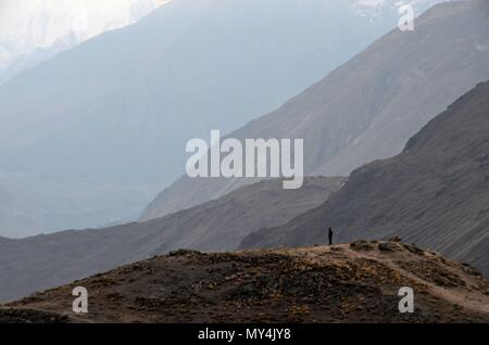 Lone individual watches sunrise among mountain peaks with layers of sunlight in Hunza Valley Pakistan - Stock Photo