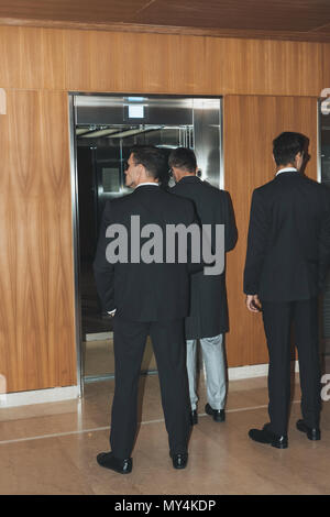 rear view of bodyguards and politician standing at elevator - Stock Photo