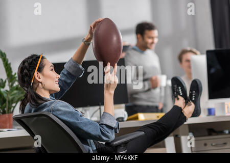 happy young woman resting with ball at office - Stock Photo