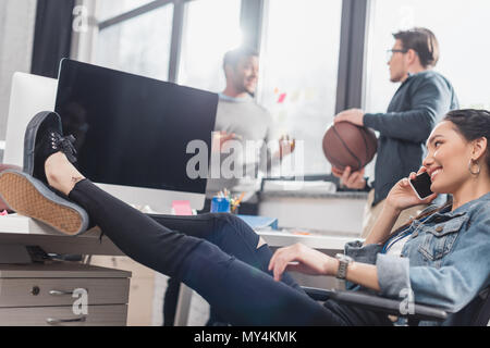 woman speaking on smartphone infront of men with ball at office - Stock Photo