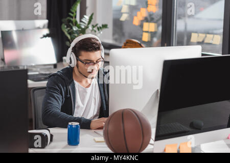 serious young man working on computer at modern office - Stock Photo