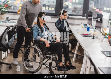 woman in wheelchair using virtual reality glasses at modern office
