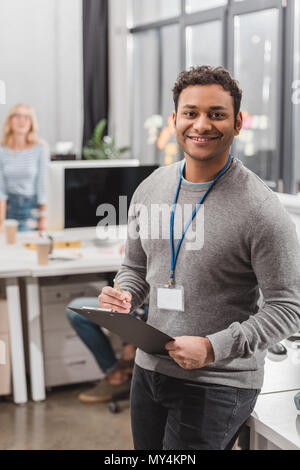 happy african american man with name tag writing something on planchette at modern office - Stock Photo
