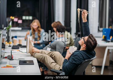 young workers eating thai food at modern office - Stock Photo