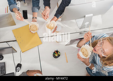 top view of cropped hands with thai food over working table at modern office - Stock Photo