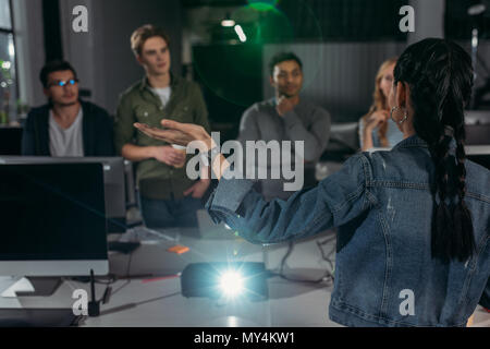 young people watching presentation in modern office, woman pointing on screen - Stock Photo