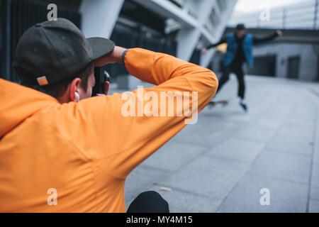 close-up shot of man taking photo of skateboarder doing trick - Stock Photo
