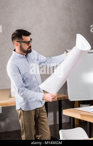 handsome architect looking at blueprint in office - Stock Photo