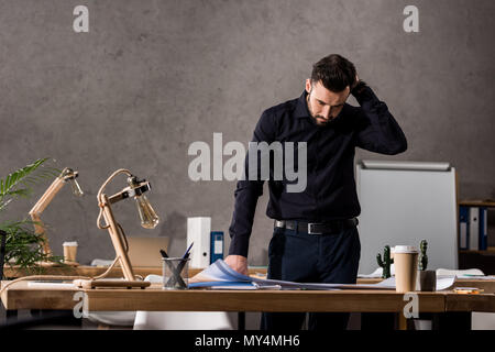 thoughtful architect standing near working table and looking at blueprints - Stock Photo