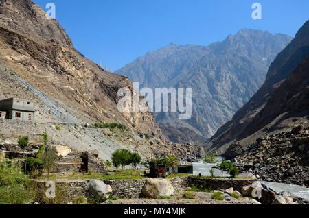 House in valley by riverside and hanging laundry amidst mountains Skardu Gilgit-Baltistan Pakistan - Stock Photo