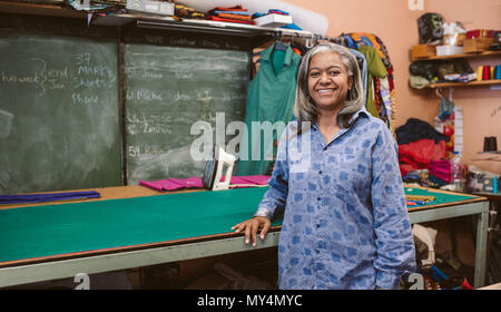 Portrait of a smiling mature seamstress standing by a table in her fabric workshop surround by sewing equipment - Stock Photo
