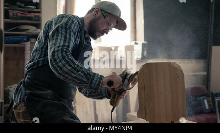 Сarpenter in work clothes and small buiness owner working in woodwork workshop, processes the board with an angle grinder , on the table is a hammer a - Stock Photo