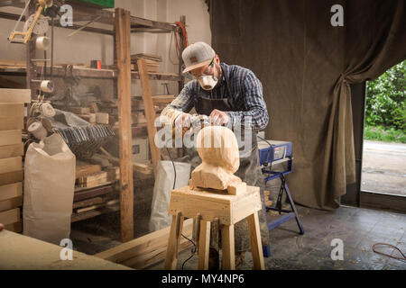Close up  young man carpenter in a suit, goggles   saws a man's head with a tree , using an angle grinder  in the workshop, around a lot of tools for  - Stock Photo