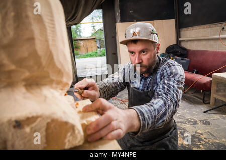 Young man carpenter in a work clothes  saws a man's head with a tree , using a chisel  in the workshop, around a lot of tools for work - Stock Photo