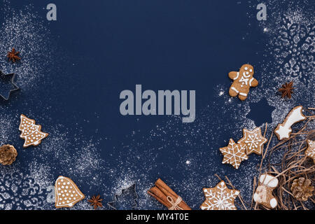 Christmas background with gingerbread and snow on navy colored surface. Holiday mood card. Top view, copy space. - Stock Photo