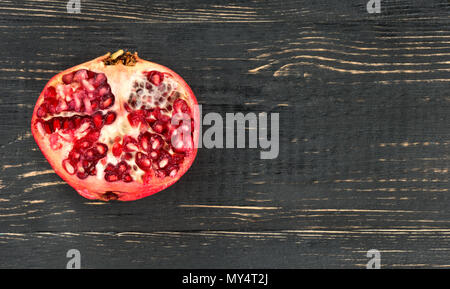 Juicy half of pomegranate on a blank wooden background - Stock Photo
