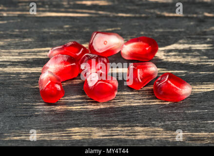 Ripe pomegranate seeds scattered on a wooden background close up - Stock Photo
