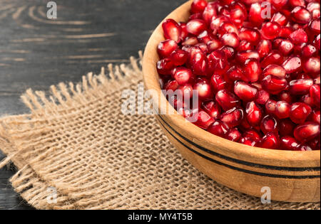 Part bowl filled with pomegranate seeds on sacking close-up - Stock Photo