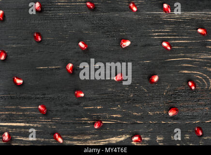 Ripe pomegranate seeds scattered on a wooden background, top view - Stock Photo