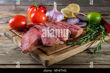 Red grouper on a cutting board with spices and vegetables. - Stock Photo