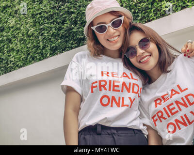 Close up Happy Portrait of Best Friends Wearing Same White Real Friend Only Concept Shirt and Sunglasses Laughing Together on Summer - Stock Photo