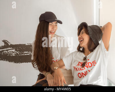 Close up Happy Portrait of Best Friends Wearing Same White Real Friend Only Concept Shirt and Hat Laughing Together in The Cafe on Summer - Stock Photo