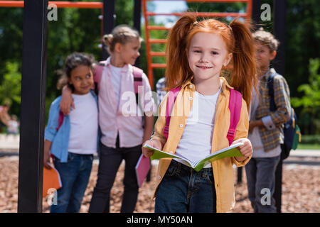beautiful red haired girl holding book and smiling at camera on playground - Stock Photo
