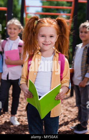 cute red haired girl holding book and smiling at camera on playground - Stock Photo