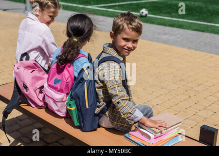 back view of cute little schoolchildren with books and backpacks sitting together on bench - Stock Photo