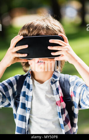 cute little boy using virtual reality headset outdoors - Stock Photo
