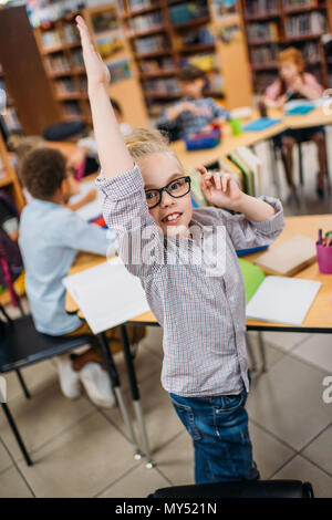 cute little girl raising hand in library - Stock Photo