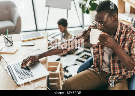 african american businessman drinking coffee while little son drawing on floor in office - Stock Photo