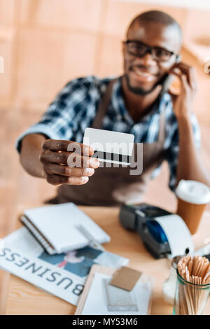 selective focus of african american man showing credit card in coffee shop - Stock Photo