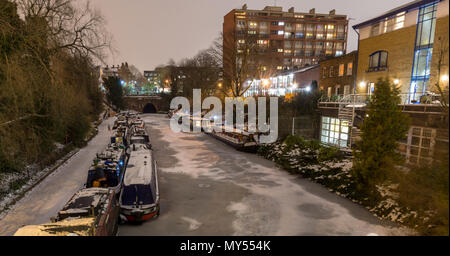 London, England, UK - March 1, 2018: Canal boats are moored in the frozen waters of the Regent's Canal, beside a snow-covered towpath in London's King - Stock Photo
