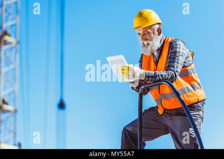 Smiling worker in reflective vest and hardhat using digital tablet - Stock Photo
