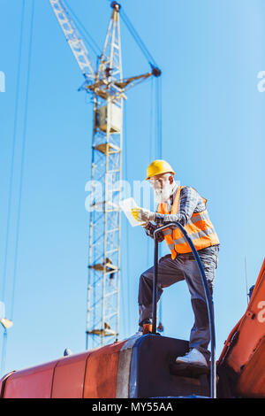 Smiling worker in reflective vest and hardhat using digital tablet while standing on top of excavator cabin - Stock Photo