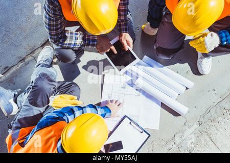 Three construction workers sitting on concrete and discussing building plans - Stock Photo
