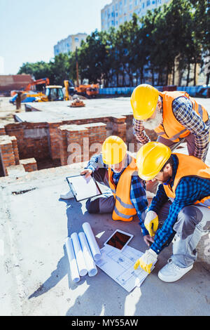 Three construction workers in hardhats sitting on concrete at construction site, examining building plans - Stock Photo