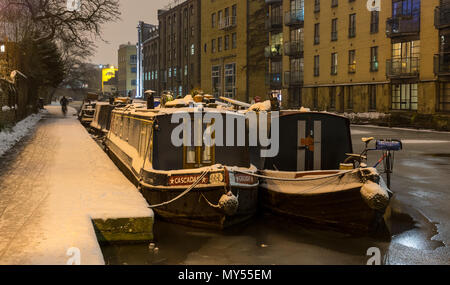 London, England, UK - March 2, 2018: Canal boats are moored in the frozen waters of the Regent's Canal, beside a snow-covered towpath in London's King - Stock Photo