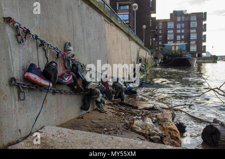 London, England, UK - January 14, 2014: Shoes found littering the tidal shores of the River Thames are strung up along the embankment of Battersea Riv - Stock Photo