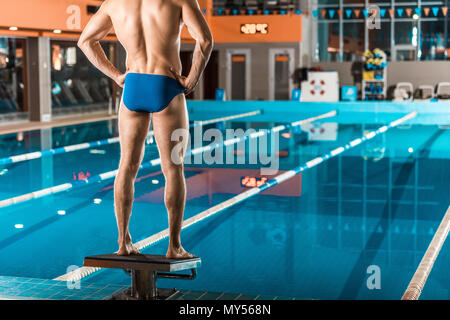 back view of muscular swimmer in swimming trunks standing at swimming pool - Stock Photo