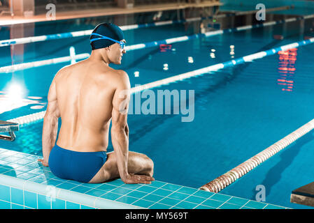 rear view of muscular swimmer in swimming cap and goggles sitting at swimming pool - Stock Photo