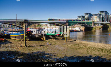 London, England, UK - May 14, 2014: A London Overground train crosses the River Thames between Imperial Wharf and Battersea on the West London Line ra - Stock Photo