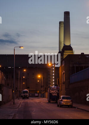 London, England, UK - May 16, 2014: The chimneys of the Battersea Power Station are lit up in the twilight in south west London. - Stock Photo